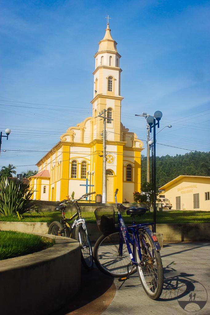 Nossas bikes estacionadas na praça com a igreja matriz de fundo